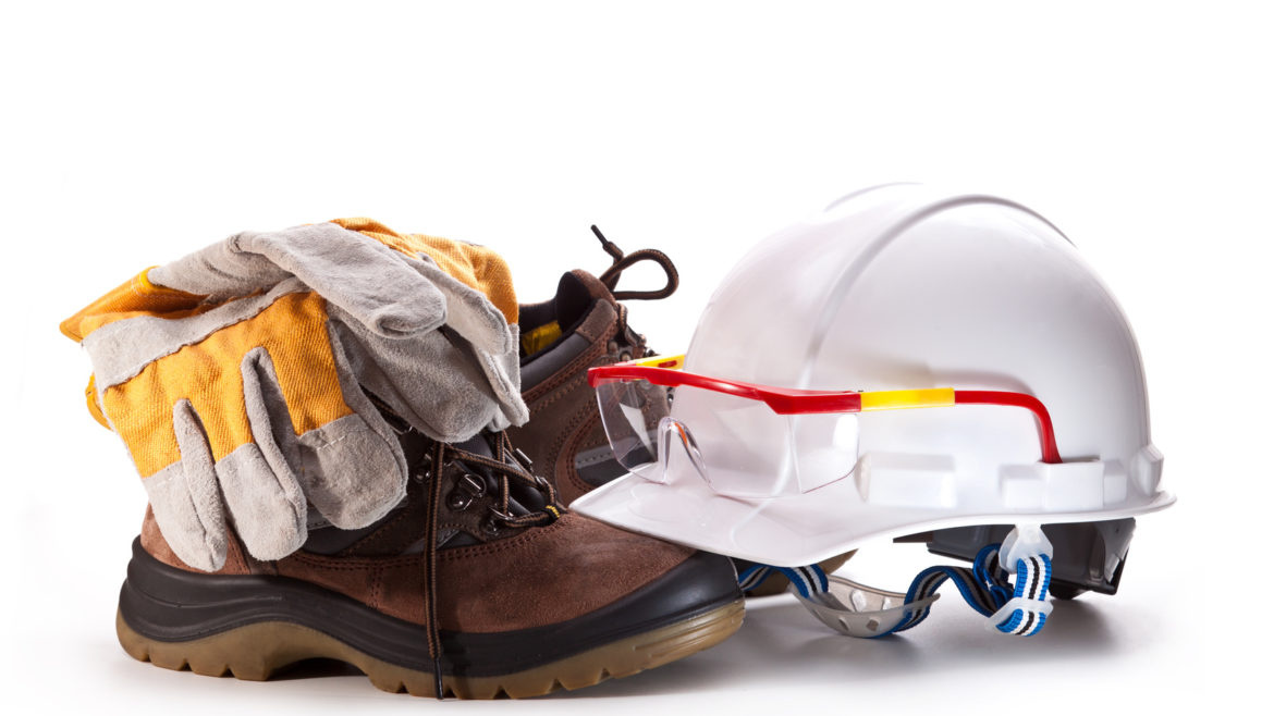 White hard hat with goggles, boots, and gloves on a white background